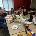Oppilaat istumassa teepöydän ääressä.
