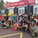 Oppilaat ovat ryhmäkuvassa tehtaan kaupan edessä.