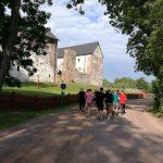 Oppilaita kävelemässä hiekkatietä kohti ylempänä olevaa linnaa.