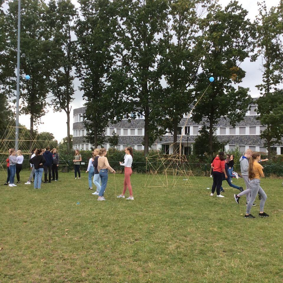 Oppilaita seisomassa pienissä ryhmissä nurmikentällä.