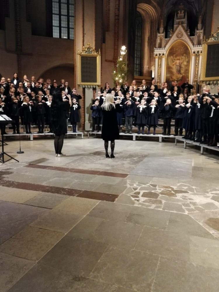 Koulun kuorot Tuomiokirkossa kuorokorokkeilla laulamassa. Kuoronjohtajat edessä johtamassa.