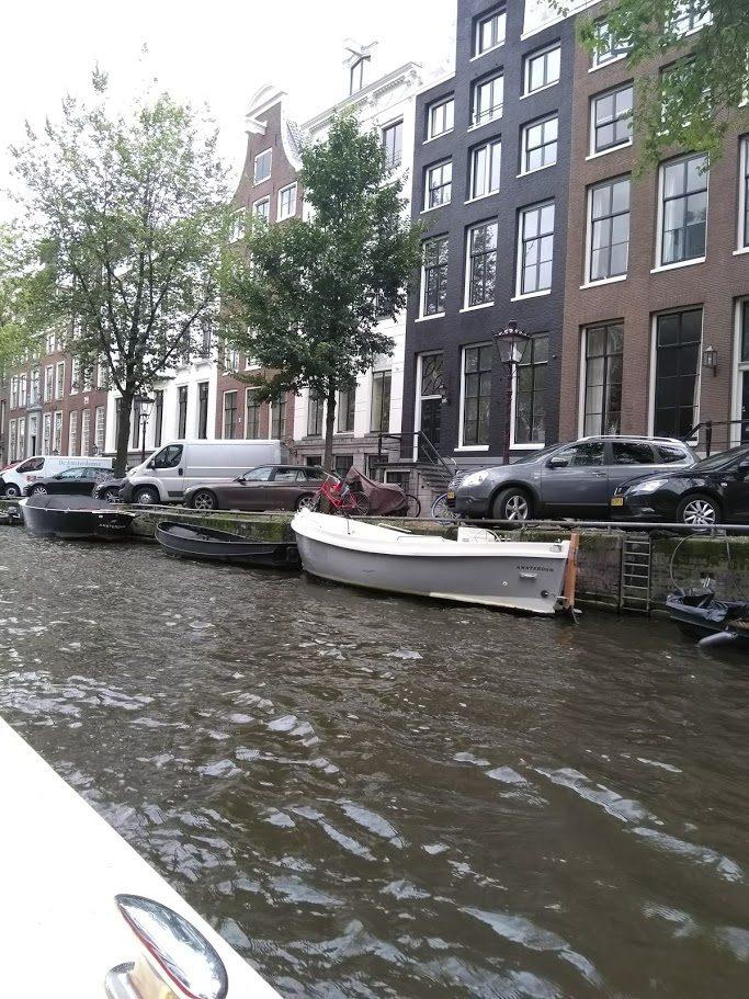 Kanavassa vesi virtaa. Toisella kanavan reunalla veneitä ja ylempänätiellä autoja parkissa.