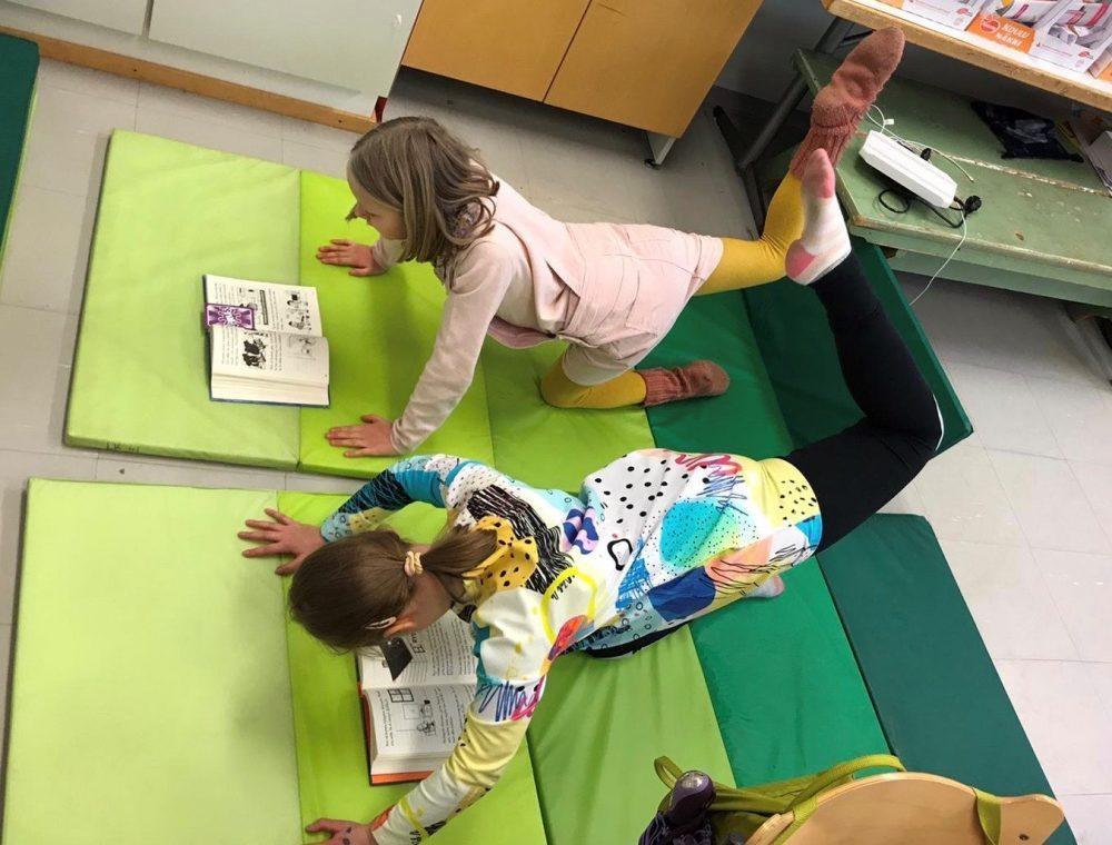 Kaksi tyttöä konttausasennossa venyttelemässä makuualustan päällä, samalla kirjaa lukien.