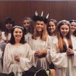 Valkoisiin pukautuneita Lucia-neitoja.