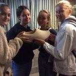 Neljä tyttöä pitävät yhdessä käsissään isoa hollannikasta.