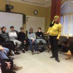 Jamaikalainen Amina eläytyen tarinaa kertomassa. Oppilaat kuuntelevat taustalla.