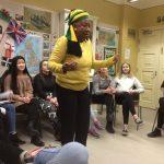 Jamaikalainen Amina tarinaa kertomassa. Oppilaat kuuntelevat taustalla.