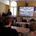 Katalonialaista ihmistornien rakennusta. Kuvassa ohjeistus isolla näytöllä. Oppilaat seuraavat opetusta.