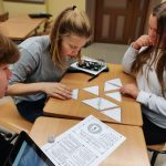 Kaksi oppilasta pulpetin ääressä pelaamassa kolmion muotoisilla pelikorteilla.