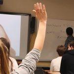 Oppilas viittaa. Kuva takaapäin.