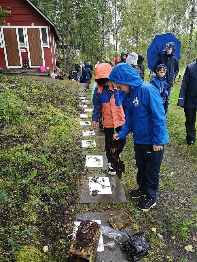 A-luokan oppilaita tutkimassa Harvaluodon maastosta löytyneitä asioita.