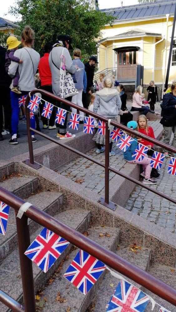 Ison-Britannian lippuja portaikon kaiteessa ja osallistuvia lapsia portailla.