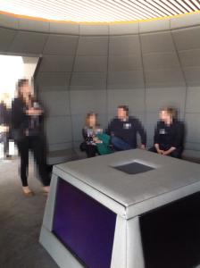 Keskikonsolissa on neljä näyttöä eri suuntiin. Opettaja istuu muiden joukossa.