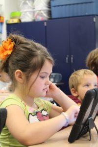 Kuvassa tyttö käyttää iPadia. Taustalla on muita lapsia.