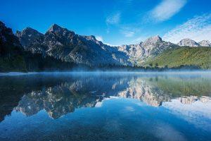 Kuvassa vuoristomaisema joka peilautuu kuvan etuosassa olevaan tyyneen veteen.